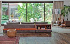 De costas para a entrada da casa, o sofá da Micasa tem um truque. A parte de trás tem banco e nichos na cor laranja, fazendo com que a composição não fique feia. Projeto do Estúdio Casa Um