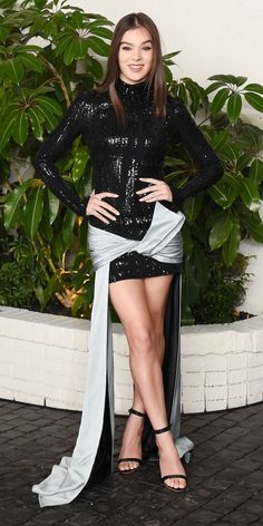 Hailee Steinfeld celebrated her nomination at a pre-Golden Globes party by bringing drama with her Atelier Versace design, featuring a sequined black long-sleeve mini and ground-grazing satin sashes knotted at her hips