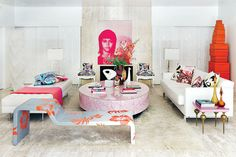 A Russell Young screen print of Jane Fonda watches over the expansive TV room, where Pucci pillows line custom white leather daybeds. A gray fiberglass Cappellini daybed painted with orange hibiscus sits beside an oversized Karim Rashid pink coffee table. In the corner, Eshaya created a sculpture from stacked Hermès boxes.