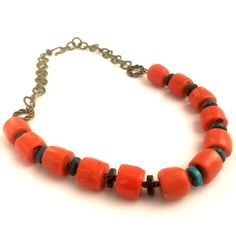 The 'Calypso' is a colourful and contemporary statement necklace featuring natural orange coral and chrysocolla rondelles, finished off by antique brass connectors, chunky link chain and hook and eye fastening. This is a beautiful fashion accessory.
