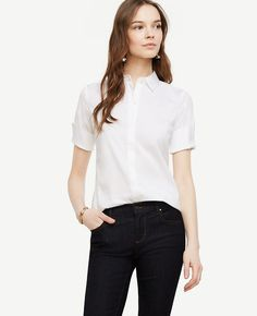 """In crisp poplin, our short sleeve button-down is a perfect transitional piece - finished with a touch of modern stretch for impeccable fit. Point collar. Elbow sleeves with slit cuffs. Hidden button front. Back yoke. Shirttail hem. 26 1/4"""" long."""