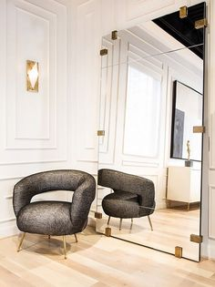 Modern retail space with traditional crown molding details, a large mirror, and a armchair