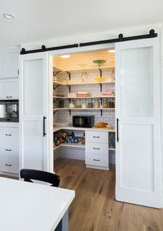 Walk-in kitchen pantry behind a sliding barn door #modern #rustic