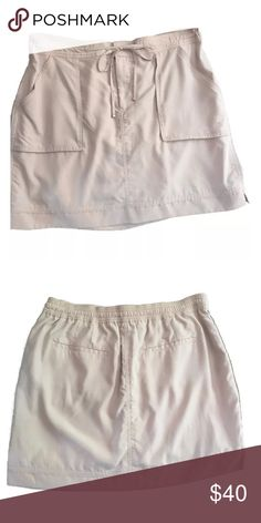 """White House Black Market Khaki Cargo Skirt NWT Casual cool with utility vibe— super soft challis skirt with velvety smooth feel is the epitome of laid-back elegance. Sits at the waist. Double hook and bar closure with interior secure button and zip fly. Functional drawstring at front with elasticized waistband at back. Front patch pockets with grosgrain details. Back welt pockets. Vented hem. 78% modal, 22% polyester. Machine wash.  Regular: Approximately 17.25"""" center back length. White…"""