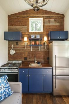 The key to making such a bold design work in a small space is balance. Here, you'll find that some spaces are painted bright white to contrast with the indigo paint and reclaimed barn wood seen throughout the house. But perhaps our favorite room of all is the kitchen where blue cabinets are paired with rustic wood instead of subway tile, which would have been the safer option. And did we mention there's shiplap on some of the walls?