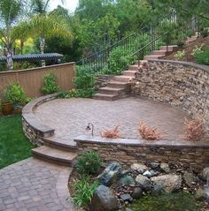 Our fire pit will look slightly like this, but no retaining wall or stairs, just a sitting wall. I like how the rocks and greens look with the pavers, but don't like the pond.
