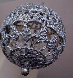 zilvergrijze kerstbal: Gehaakte kleedjes van ongebleekte katoen gehaakt en gedrapeerd over een ballon. En daarna aan elkaar gezet. Verstevigd met verdunde houtlijm. Vervolgens geschilderd met zwart en zilver