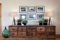 A gallery wall above an antique wood console features vintage black and white photos of the home and property in years past.