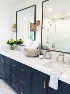 Chic bathroom design with white marble countertops and navy cabinets. The antique brass sconces are perfect in this space.