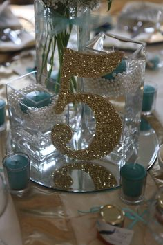 Table decor/centerpieces included rectangular glass vases from David's Bridal in 3 sizes, filled with pearl filler from Save-on-Crafts, water and floating candles in aqua green from Yummi Candles. Votives were also placed around the table. Satin and tulle embroidered table runners in Champagne were purchased from Smarty Had a Party. Mirrored centerpieces, votive holders , and ivory linens were provided by the venue. Gold glitter table numbers were handmade by the bride and bridesmaids.