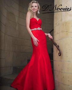 Vestido corte sirena en tafeta roja con un sobrio cintillo de cristales en la cintura.