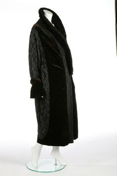 A fine black beaded velvet opera coat, 1920s. the dark brown/black ground with ruched and padded shawl collar, flounces to cuffs, the ground entirely covered in black bugle beads in flame-like formations, the shoulders and front bands in faceted irridescent seed beads, lined in shocking pink silk moire