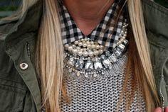 Layers of statement necklaces, under a buttoned up collar.
