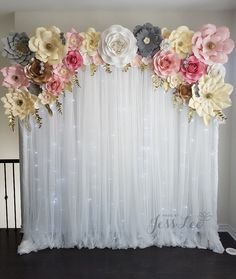 Paper flower backdrop with fairy lights. Pink, grey, white, champagne, and ivory paper flowers with gold leaves.