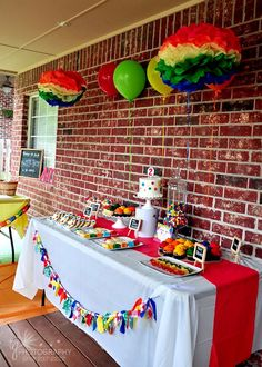 rainbow colored art painting studio birthday party dessert table with tissue poms and balloons