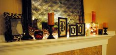 """The mantle - a picture of last year's Halloween costumes, spooky lighted garland and candles, and a newly-made """"Boo"""" sign out of vinyl lettering, backless frames and Halloween scrapbook paper. Oh, and some spiderweb fabric draped over the mirror."""