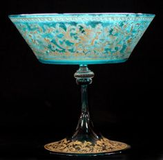 Probably Murano glass comport in green and clear glass with gilt decoration of nudes in flower heads. Height 20 cm; 'antique' but no other date available.
