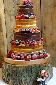4 tier naked cake decorated with fresh fruit and personalised Bride and Groom cake topper, at Blake Hall in Essex