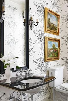 Along with its black marble sink surround and painted black-framed mirror, the handsome powder room features a whimsical tree-patterned wallpaper.
