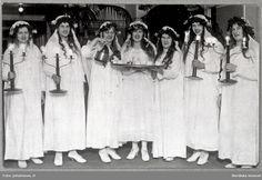 Luciafest på Sala lasarett 1921 med skämtsamt inslag. Lucia i mitten med bricka i hand omgiven av sina tärnor. Deltagarna i tåget är sannolikt personal på lasarettet som ska uppvakta patienterna.
