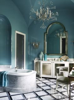 The tub in the master bath is by Jacob Delafon, with fittings by Waterworks, the sconces are by Niermann Weeks, and the Veere Grenney chair is covered in an Armani/Casa fabric; the chandelier is by Tony Duquette, and the vanity, mirror, and marble flooring are all custom designs. - ELLEDecor.com