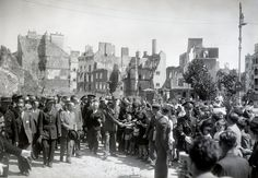 General Charles de Gaulle (center) shaking hands with children, two months after the German capitulation in Lorient, France, in July of 1945.