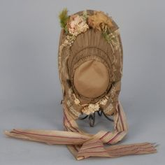 Olive green decorated with lace, cloth flowers and feathers along outer and underside of brim having open strips of silk, striped silk ties, lace trimmed bavolet with cloth flowers.