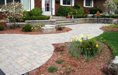 Photo by Dennis Miller. Tumbled paving stone walkway with precast concrete retaining wall and steps.
