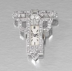 DIAMOND DRESS CLIP WATCH, 1930S. The rectangular dial applied with baton indicators inset to a geometric open work case millegrain set with circular-, single-cut and baguette diamonds, French import marks, fitted case by Boucheron Paris.