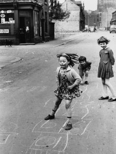 Three girls play hopscotch in the middle of the street in Moss Side, Manchester…. Three girls play hopscotch in the middle of the street in Moss Side, Manchester. A small cornershop grocers is visible back left.
