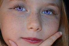 Violet eyes, red hair, freckles (beautiful, but likely fake - violet eyes would be seen on someone with pale or variated skin color, due to incomplete albinism, otherwise violet eyes are a light effect on dark blue eyes)