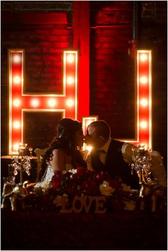 Husband and wife share a kiss in front of their custom circus-theme light up intials. The Mitten Building, Redlands CA New Year's Eve 2014. www.rachaelhallweddings.com