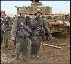 German Grenadiers carrying a casualty in an improvised stretcher, behind them is a Panzer IV Ausf.G Nr. 212 of Panzer-Abteilung 21, 20th Panzer Division. Russia, January 1944