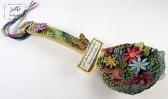 An altered wooden spoon full of flowers.        The flowers are made from air dry clay.   Also, I used a piece of tulle.       The flowe...