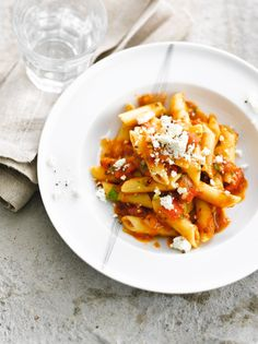 Bereiden: Leg de tomaten 6 sec. in kokend water en schrik meteen in ijswater. Pel de tomaten, verwijder de zaadlijsten en snijd ze in stukjes. Snijd de ui en knoflook fijn. Laat de geroosterde paprika uitlekken en snijd in kleine stukjes. Hak de peterselie en basilicum fijn. Verkruimel de feta. Snijd de chilipepertjes in twee en verwijder de zaadlijsten. Kook de pasta in gezouten water al dente. Fruit de ui en de knoflook in een pan. Voeg de blokjes tomaat, passata, geroosterde paprika en…