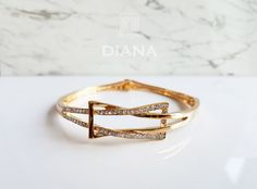 The intertwined ribbon of sparkling crystals that forms a bow adds a regal touch to this gold bangle. Visit our collection today for a full range of beautiful women's fashion accessories. Gold Bangles, Gold Rings, Diana, Fashion Accessories, Sparkle, Wedding Rings, Rose Gold, Engagement Rings, Crystals