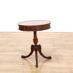 This drum table is featured in a solid wood with a glossy mahogany finish. This traditional style side table has a carved pedestal, tri-cabriole leg base, and single spacious drawer. Perfect for holding plants! #americantraditional #tables #endtable #sandiegovintage #vintagefurniture