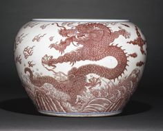 A RARE COPPER-RED AND UNDERGLAZE-BLUE DECORATED 'DRAGON' FISH BOWL QING DYNASTY, KANGXI PERIOD the sturdily potted bowl with deep sides gently curving up to the lipped rim, the exterior painted in underglaze-red with two ferocious five-clawed dragons striding in pursuit of flaming pearls, all amidst flames and clouds and above breaking waves, the dragon's eyes in underglaze-blue Ceramic Bowls, Glass Ceramic, Porcelain Ceramics, China Porcelain, Copper Red, Chinese Ceramics, Qing Dynasty, Oriental, Dragon Fish