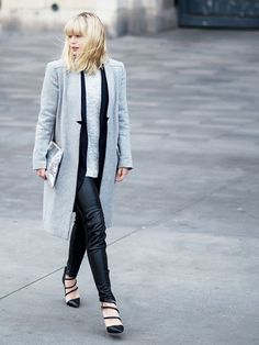 Lisa Dengler wears a gray sweater and black sweater layered under a gray coat, paired with leather skinny pants, a metallic clutch, and strappy black pumps