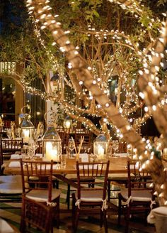 Small incandescent lights dot trees creating an ethereal atmosphere for this outdoor affair.