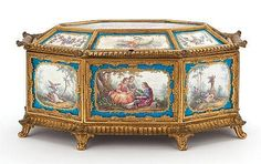 A FRENCH SÈVRES-STYLE PORCELAIN OCTAGONAL CASKET WITH GILT BRONZE MOUNTS  Probably Paris, France, circa 1900 Marks: spurious Sèvres marks to plaque backs 7 x 14 x 10 inches (17.8 x 35.6 x 25.4 cm)   The octagonal casket with seventeen porcelain plaques with gilt blue borders, pastoral scene at top bordered by plaques of floral swags and trophies, pastoral scene to front and back center, end panels depict winged putti on clouds alternating with pastoral still lifes, gilt bronze mounts ...