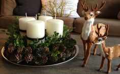 Candles with pine cones on round tray