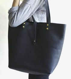 4f660bcfb3ae Crafted from thick, pebbled oil hide leather, this black tote bag is an  excellent