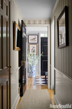 The high-gloss oil finish of Benjamin Moore's Black on the doors, and Pratt & Lambert's Moselle on the trim, adds polish to the entry and hallway.   - HouseBeautiful.com