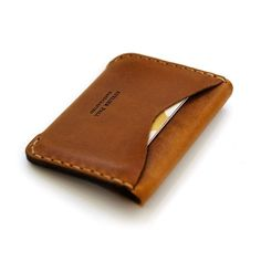 The Flap Leather Wallet is a slim minimal wallet handcrafted from a single piece of high quality leather. The edges are hand polished and burnished with beeswax. Featured with a classic flap enclosure fastened by two antique brass finish snaps, this carefully hand stitched leather wallet accommodates more than 8 credit cards, coins and bills folded in half. The chestnut pattern of the leather gives it a unique aspect. The compact minimal design and the light chestnut brown color of the…