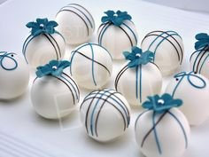 Custom cake balls with teal flowers and brown drizzles.