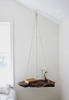 Hanging Book Shelf - Drill three holes in a slab of wood, thread some rope through and tie a knot at each end. Hang the suspended slab of wood via a hook screwed into a ceiling beam and you've got yourself a beautiful alternative to a table.