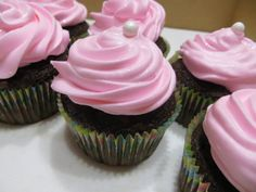 Chocolate cupcakes with swirled raspberry-flavored buttercream frosting topped with edible pearls and edible glitter