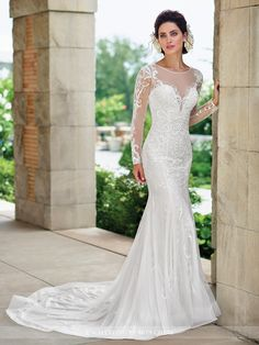 Lace and tulle fit and flare gown with illusion lace long sleeves and jewel neckline, deep plunging sweetheart bodice with hand-beaded lace motif and dropped waist, illusion lace back with covered buttons, horsehair hemline, chapel train. Sizes: 0 – 20 Color: Diamond White