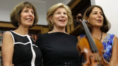 Sisters Jill Totenberg, left, Nina Totenberg, center, and Amy Totenberg pose for pictures with the Ames Stradivarius violin during a news conference in New York, Thursday, Aug. 6, 2015.